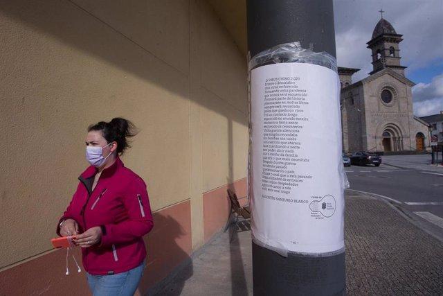 Una mujer camina frente a una farola donde hay pegado un papel con un poema titulado 'El virus chino 2020', en el municipio gallego de Guitiriz, en Lugo, Galicia (España), a 17 de febrero de 2021
