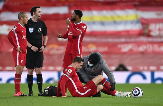 20 February 2021, United Kingdom, Liverpool: Liverpool's Jordan Henderson is checked by medical staff after picking up an injury during the English Premier League soccer match between Liverpool and Everton at the Anfield stadium. Photo: Laurence Griffiths