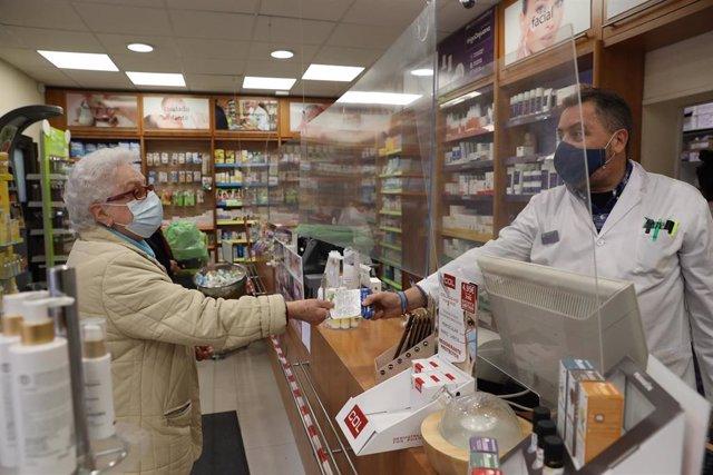 Una anciana recoge una mascarilla FFP2 en la farmacia situada en la C/Tucán (Carabanchel), en Madrid (España), a 4 de febrero de 2021. Los mayores de 65 años de la Comunidad de Madrid pueden recoger a partir de hoy la primera de las dos mascarillas FFP2 q