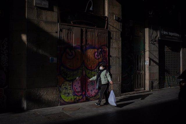 Archivo - Una mujer camina con una bolsa de basura por una calle del centro de Barcelona, Catalunya (España), a 26 de octubre de 2020.
