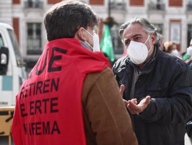 """El portavoz socialista, Pepu Hernández, conversa con un hombre que acude con una camiseta donde se puede leer """"Que retiren el ERTE de Ifema""""."""