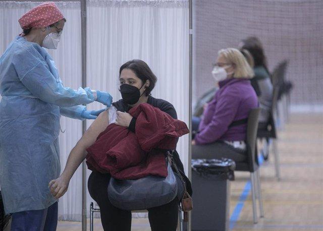 Personal sanitario durante la administración de la primera dosis de la vacuna AstraZeneca contra la Covid-19 al personal de servicio de ayuda a domicilio en las instalaciones deportiva del pabellón Sadus de la Universidad de Sevilla. En Sevilla (Andalucía
