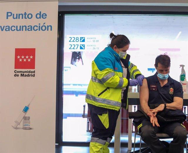 Una sanitaria vacuna a un bombero de la Comunidad de Madrid en el punto de vacunación contra el Covid-19 puesto en marcha en el Estadio Wanda Metropolitano el primer día de su funcionamiento, en Madrid (España), a 25 de febrero de 2021.