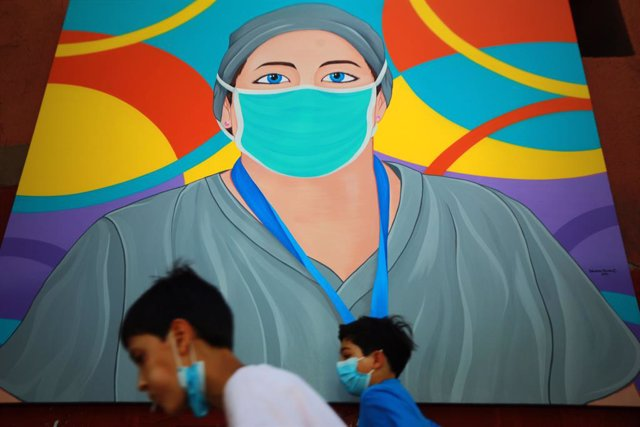 25 February 2021, Chile, Santiago: Children walk past one of more than 30 paintings made by the artist Sebastian Duran recognising the ongoing efforts of the Chilean frontline services during the coronavirus pandemic. Photo: Jose Francisco Zuniga/Agencia
