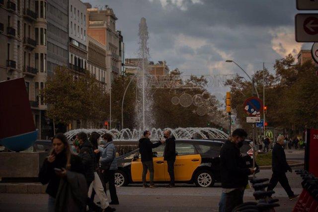 Archivo - Personas alrededor de un taxi, en Barcelona, Catalunya (España), a 25 de noviembre de 2020.