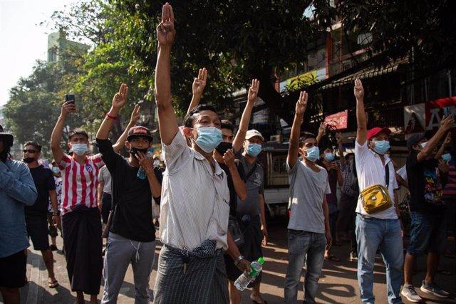 Manifestantes realizan el saludo de los tres dedos alzados propio de los defensores de la democracia en Rangún, la ciudad más poblada de Birmania en una nueva jornada de protestas contra el golpe militar.