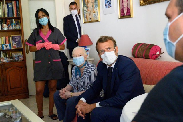Archivo - 04 August 2020, France, Toulon: French President Emmanuel Macron (2nd R) visits 80-year-old Gisele Charles (3rd R) who lives alone in Toulon, as part of his meetings with home carers. Photo: Christophe Simon/AFP/dpa