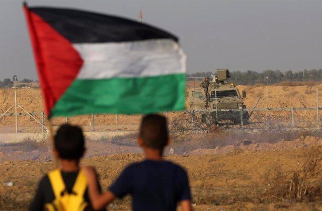 Archivo - Manifestantes palestinos con una bandera en la frontera entre la Franja de Gaza e Israel
