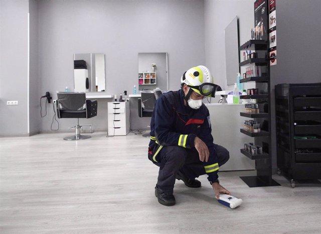 Archivo - El jefe del Servicio de Extinción de Incendios de Fuenlabrada participa en la desinfección de la peluquería Siglo XXI, dentro de la labor de limpieza del Ayuntamiento en establecimientos comerciales y colegios con máquinas de ozono, a 6 de mayo