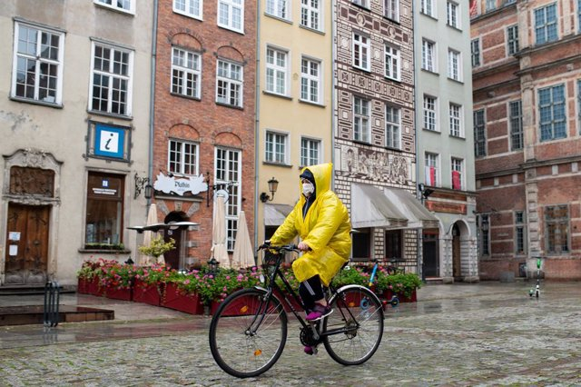 Archivo - 21 October 2020, Poland, Danzig: A woman wearing a face mask rides a bicycle on Dluga Street. Poland reported 12,107 new daily coronavirus cases on Thursday, the highest number since the beginning of the pandemic, with fresh restrictions set to