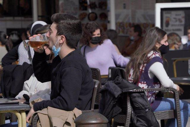 Varias personas en la terraza de un restaurante durante el primer día de la apertura parcial de la hostelería en Santiago de Compostela, A Coruña, Galicia (España), a 26 de febrero de 2021. La Xunta de Galicia reabre desde hoy parcialmente la hostelería y