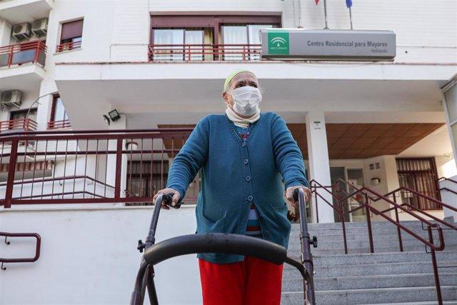 Una anciana sale de un centro residencial para mayores, durante el segundo día en el que los ancianos pueden salir a pasear. En Sevilla, (Andalucía, España), a 16 de febrero de 2021.