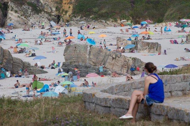 Archivo - Una persona sentada frente a la playa en A Mariña en julio de 2020.