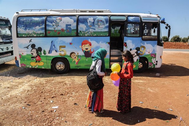 Archivo - 22 September 2019, Syria, Hazano: Syrian children are seen outside a bus which is converted into a classroom. Local teachers have invented the mobile schools to provide displaced children from rural Idlib and Hama countryside with an education.