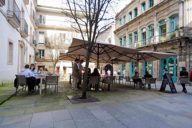 Varias personas en la terraza de un restaurante durante el primer día de la apertura parcial de la hostelería en Vigo, Pontevedra, Galicia (España), a 26 de febrero de 2021. La Xunta de Galicia reabre desde hoy parcialmente la hostelería y la movilidad en