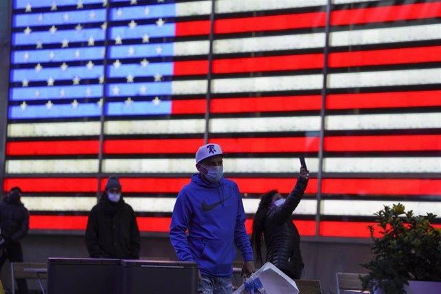 Archivo - Gente con mascarilla frente a un cartel luminoso con la bandera de Estados Unidos