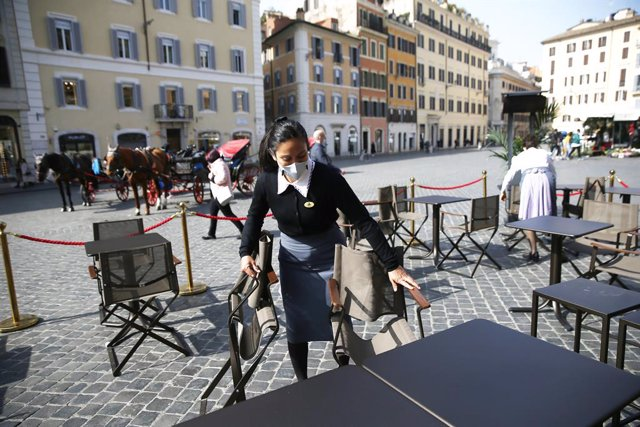 26 February 2021, Italy, Rome: An employee prepares tables in the outdoor area of a cafe near the Spanish Steps. In Italy, the number of people who have died with or from a Corona infection in one day has dropped again. Photo: Cecilia Fabiano/LaPresse via