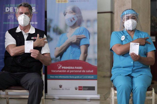 El presidente de Perú, Francisco Sagasti, y una enfermera muestran los documentos que certifican su vacunación.