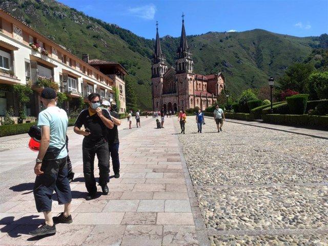 Archivo - Turistas paseando en el Santuario de Covadonga con mascarillas este verano.