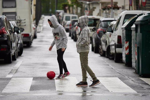 Archivo - Dos niños protegidos con mascarilla juegan con una pelota por la calle