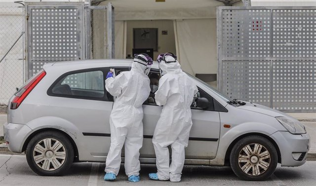 Archivo - Dos sanitarios realizan una prueba PCR a una persona desde su vehículo