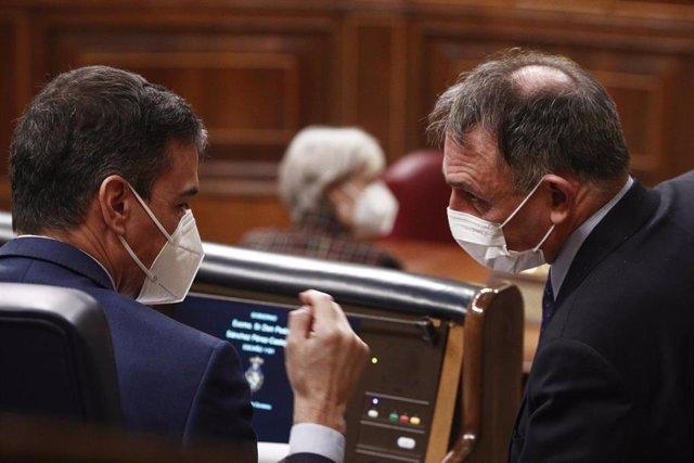 El presidente del Gobierno, Pedro Sánchez (i), conversa con el diputado de Unidas Podemos y portavoz de IU en el Congreso, Enrique Santiago, en una sesión de Control al Gobierno en la Cámara Baja, (España), a 24 de febrero de 2021.