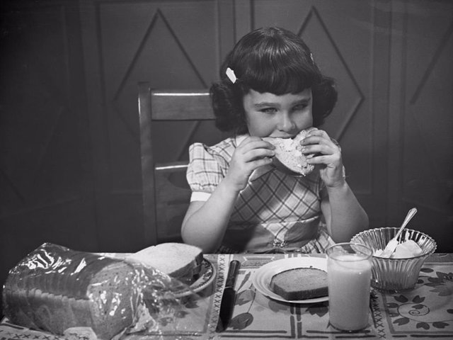 Archivo - Portrait of little girl eating buttered toast.  (Photo by George Marks/Retrofile/Getty Images)