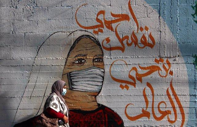 27 February 2021, Palestinian Territories, Gaza: A Palestinian woman walks past a mural in Gaza city. Photo: Mahmoud Ajjour/APA Images via ZUMA Wire/dpa