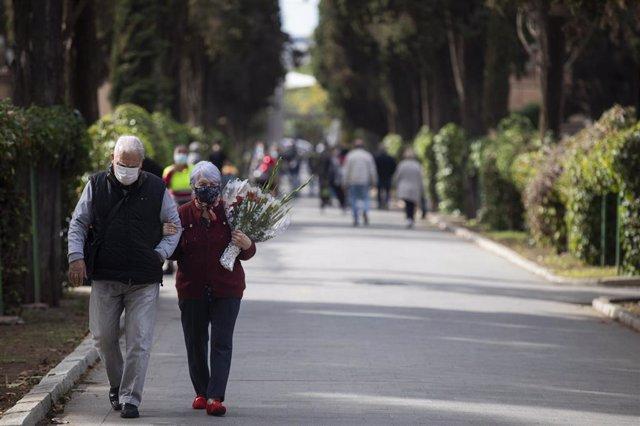 Archivo - Dos personas caminan por las instalaciones del Cementerio de San Fernando, en Sevilla.