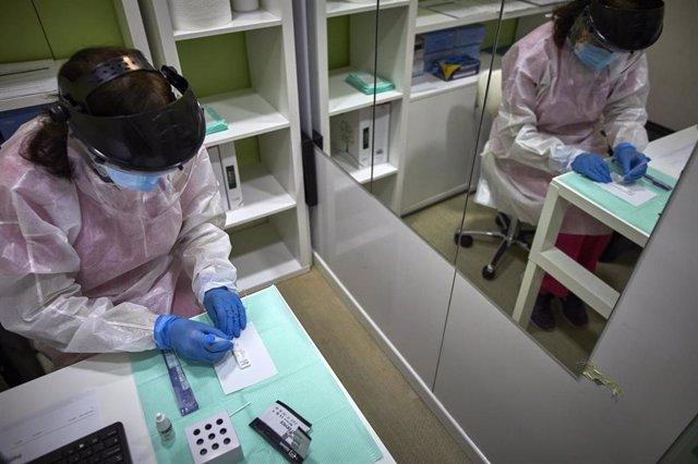 Una farmacéutica comprueba si la persona a la que le ha realizado el test de antígenos es positiva o negativa por Covid-19 en la Farmacia Las Gemelas en Madrid (España)