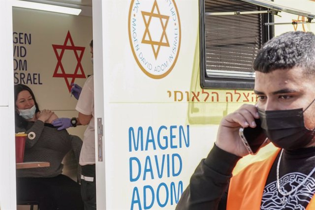 24 February 2021, Israel, Jerusalem: A woman receives her dose of the Pfizer/BioNTech COVID-19 vaccine at a mobile clinic of Magen David Adom parked at the Mahane Yehuda Market. Photo: Nir Alon/ZUMA Wire/dpa