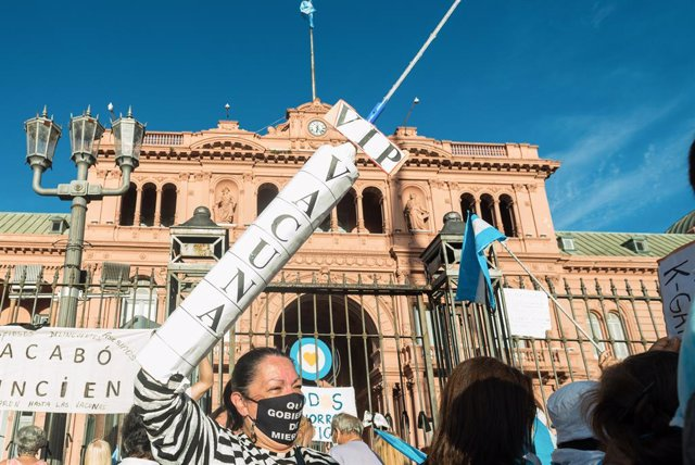 27 February 2021, Argentina, Buenos Aires: A protester holds a replica of a huge syringe during a protest against the Argentinian government after the VIP vaccine rollout scandal. The government published a list of 70 public figures who have already recei