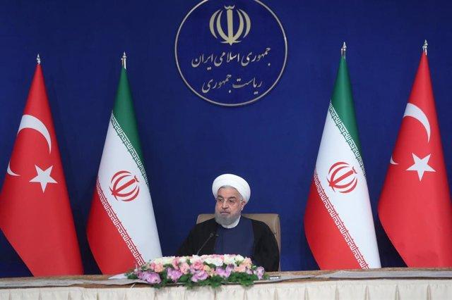 Archivo - El presidente iraní, Hasán Rohani, asiste por videoconferencia a la sexta reunión del Consejo de Cooperación de Alto Nivel entre Irán y Turquía