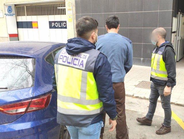 Uno de los detenidos junto con los agentes de la Policía Nacional.