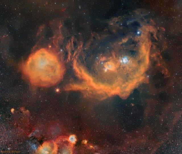La supergigante roja aparece como un estallido estelar rojo entre dos nubes naranjas.