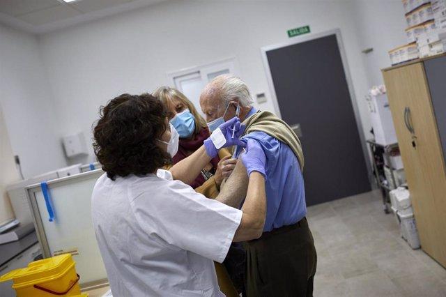Un octogenario es vacunado con la primera dosis de la vacuna de Pfizer en el Centro de Salud Andrés Mellado, en Madrid (España), a 25 de febrero de 2021.