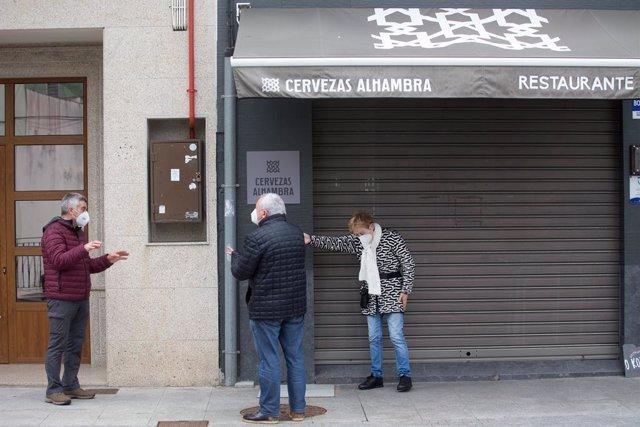 Dos personas conversan frente a un bar con las persianas bajadas en el municipio de Guitiriz, Galicia.