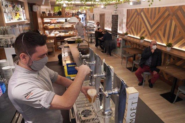 Un camarero llena un vaso de cerveza en un restaurante