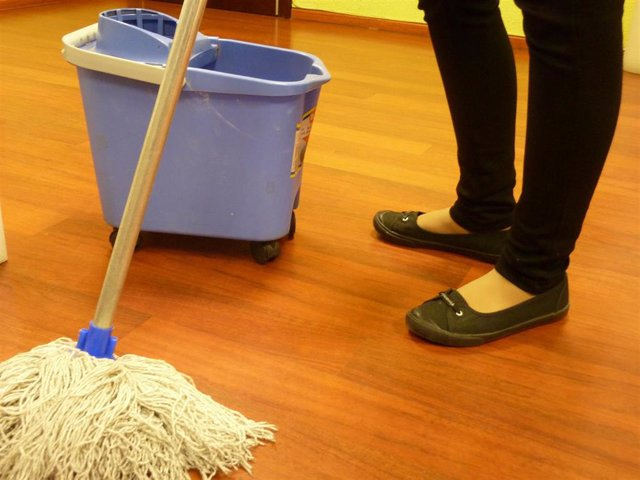 Archivo - Una mujer limpiando el suelo con una fregona.