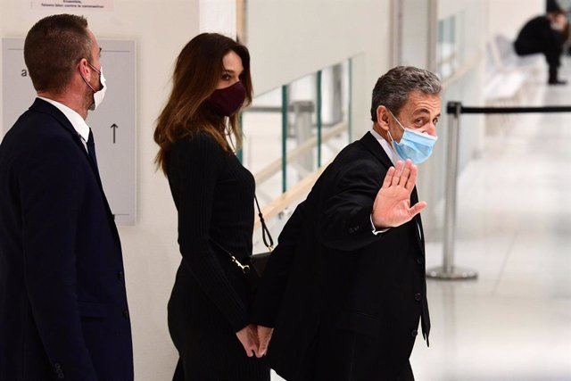 Archivo - 09 December 2020, France, Paris: Former French President Nicolas Sarkozy (R) leaves Paris' courthouse with his wife Carla Bruni-Sarkozy after a hearing of his trial on corruption charges. Photo: Martin Bureau/AFP/dpa