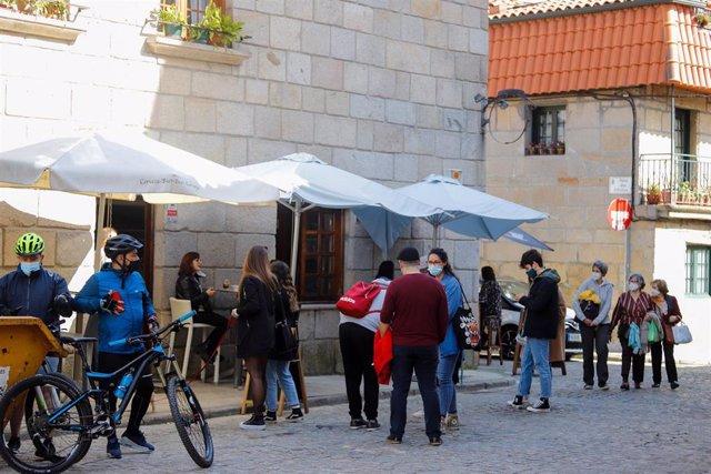Varias personas en la terraza de un bar en el barrio de Bouzas, en Vigo, Galicia (España), a 28 de febrero de 2021. Los gallegos afrontan este domingo el tercer día de desescalada progresiva después de que este viernes 26 de febrero comenzara el alivio de