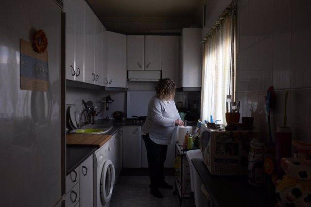 Una mujer realizando tareas del hogar en la cocina
