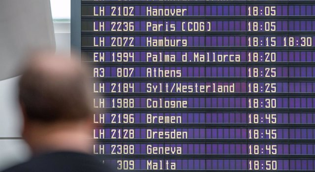 Archivo - 14 August 2020, Bavaria, Munich: A man stands in front of the departure display board at Munich International Airport.  Germany's public health agency declared the Spanish tourist island of Mallorca a coronavirus risk region following a spike in