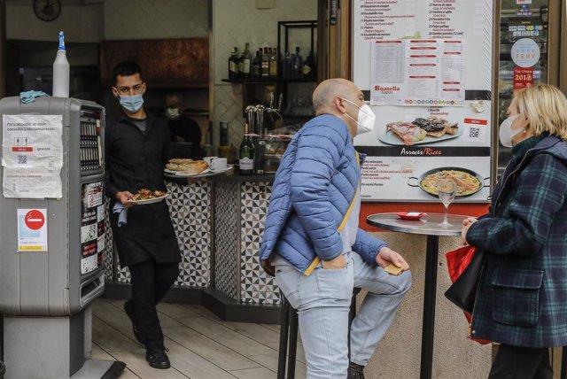 Un camarero atiende a varios clientes en una terraza el primer día de la apertura de la hostelería en Valencia en la desescalada de la tercera ola