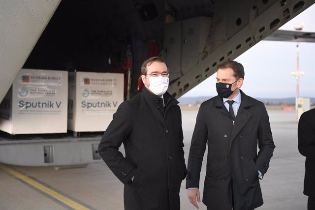 El primer ministro de Eslovaquia, Igor Matovic (D) y el ministro de Salud,  Marek Krajci (I), posan en el aeropuerto de la ciudad de Kosice ante el primer envío de vacunas Sputnik V llegado al país.