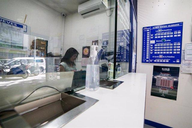 Archivo - Una dependienta trabaja en el interior de una administración de lotería de la capital con gel desinfectante para los clientes.