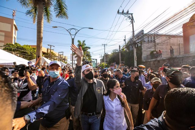 HANDOUT - 28 February 2021, El Salvador, San Salvador: Nayib Bukele (C), President of El Salvador, waves to supporters as he arrives at a polling station with his wife Gabriela Rodriguez (C-R) during the local and legislative elections in El Salvador. Pho