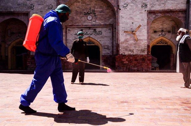 Archivo - Un trabajador realiza labores de desinfección en una mezquita en Pakistán en medio de la pandemia de coronavirus