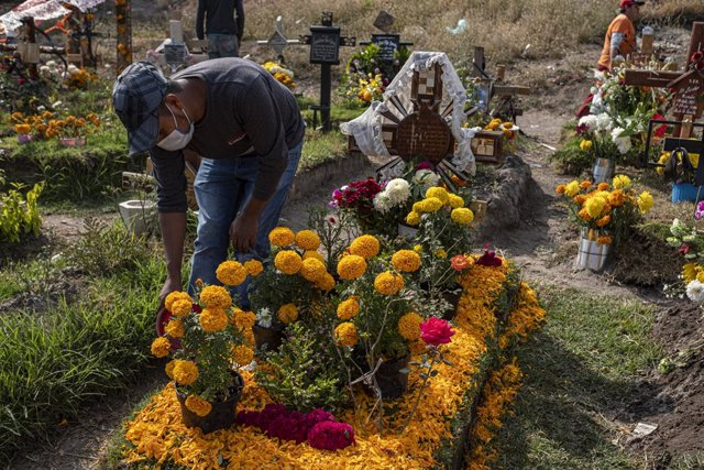 Archivo - 31 October 2020, Mexico, Chalco: A man decorates his relatives' graves with flowers, ahead of the Mexican Festival Day of the Dead. Photo: Jacky Muniello/dpa