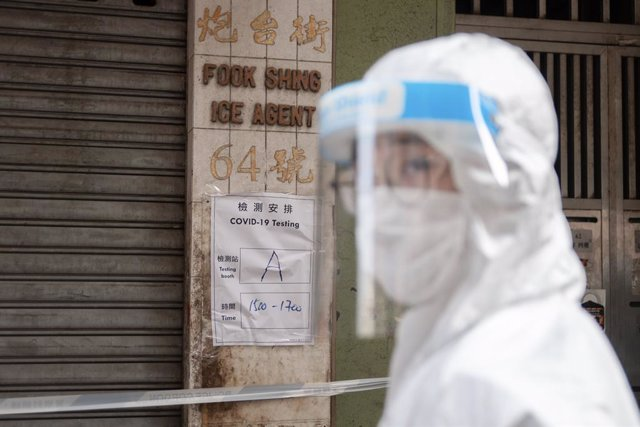 Archivo - 23 January 2021, China, Hong Kong: A health worker stands in front of a notice informing residents about time of compulsory coronavirus (COVID-19) test in a wall during lockdown imposed by the government to curb the spread of the pandemic. Photo